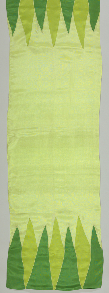 Oblong scarf of pale green silk crepe, doubled. At each end, triangular forms in medium and dark green are set in to form a border.