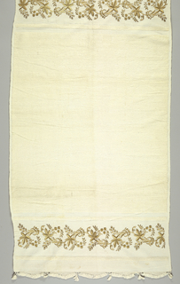 White solid looped uncut towel except at the ends, where on a border of plain weave is embroidered, in gold, a serpentine stem with five-pointed leaves and small flowers. Scalloped fringe on ends.