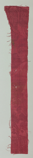 Floral pattern on strip of red fabric.