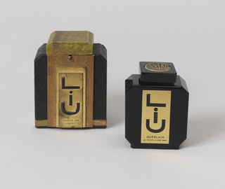 "Black glass bottle, rectangular with champfered corners, slightly raised base, paper label says ""Liu Guerlain 68 Champs Elysees Paris;"" lid of black glass, square, has round paper label ""Guerlain.""  Paper box has textured surface, similar shape as bottle & lid, label says ""Liu Guerlain Paris."""
