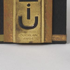 "Black glass bottle, rectangular with champfered corners, slightly raised base, paper label says ""Liu Guerlain 68 Champs Elysees Paris;"" lid of black glass, square, has round paper label ""Guerlain.""  Paper box has textured surface, similar shape as bottle & lid, label says ""Liu Guerlain Paris."""