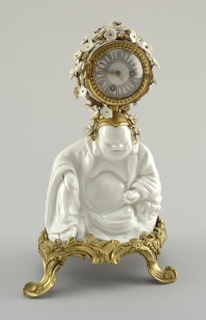 A white porcelain figure of Pu T'ai Ho-Shang on a gilt bronze four legged base; circular clock in bronze housing covered in small white porcelain flowers on top of  figure's head.