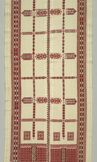 Oblong panel of handwoven off-white linen embroidered in red and green silk has borders in a geometric and imbricated design. The center has three narrow vertical floral bands that are highly stylized; these are intersected with seven horizontal bands in a floral and geometric pattern.