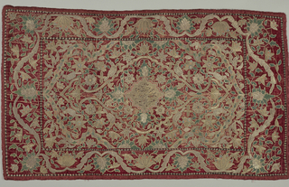 Oblong panel of red velvet embroidered in blue, orange and metallic threads. Central motif has an Arabic inscription and is surrounded by a radiating floral pattern. Border in a stylized vine and flower pattern.