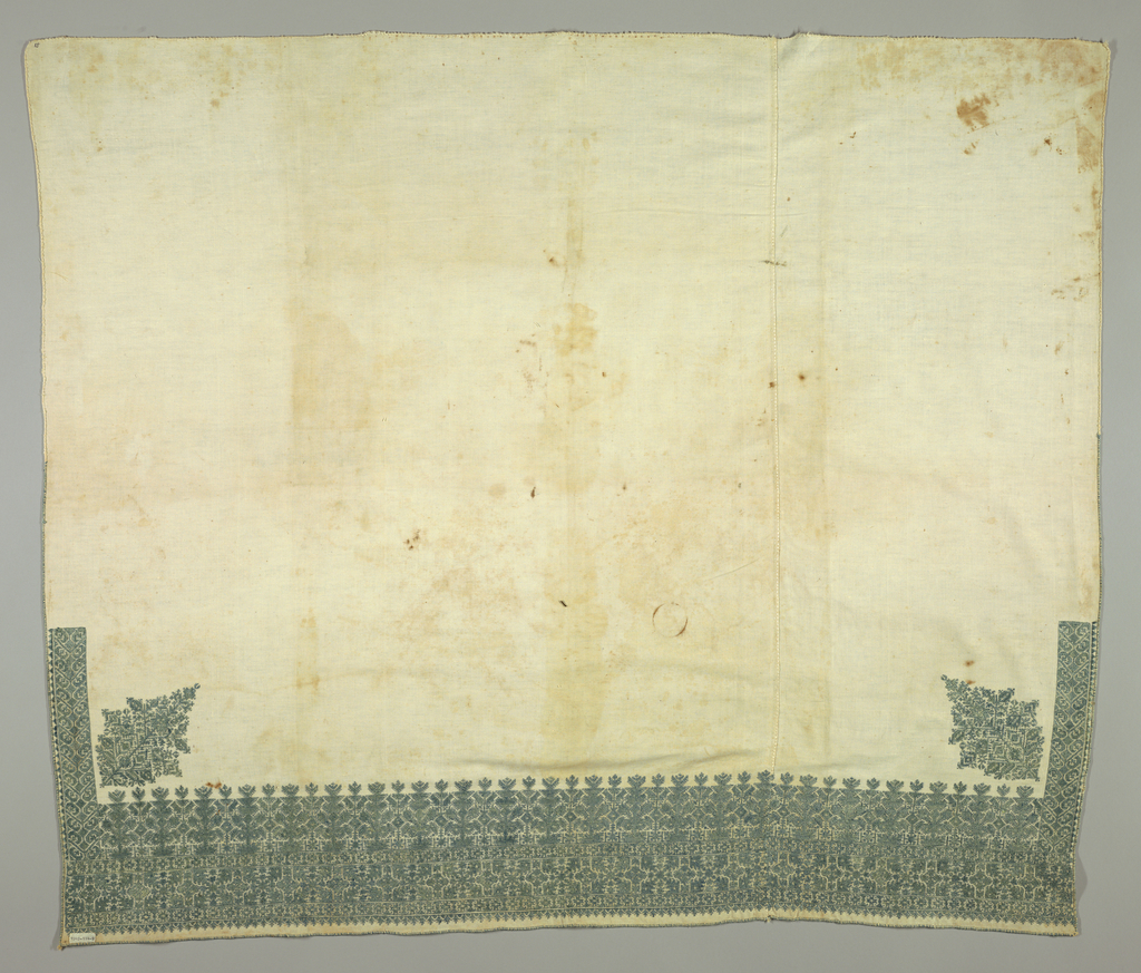 Cotton panel embroidered at one end and up part of the side in pale green silk. Border shows conventionalized geometric designs with stylized trees above.