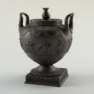 Ovoid, with high looped handles and small cylindrical neck. On square plinth (b) with relief palmette decoration, and ogee foot (d) with leaf-molded edge. Flat cylindrical cover (c) with relief palmette and guilloche decoration, and vase finial.