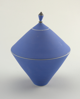 A porcelain conical vase and cover, when put together, create a diamond shape. Both vase and cover in a solid blue with a pointed knob on the lid.
