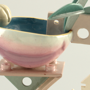 Standing cup with tall foot constructed of triangular and rectangular slabs, each triangle pierced with a circular hole; foot surmounted by a cup in the form of a 1/2 peach with small pit-like projection on one side and abstract 'handle' constructed of triangles and other smaller geometric shapes opposite. Glazed overall in shades of yellow, green, biege, and pink.