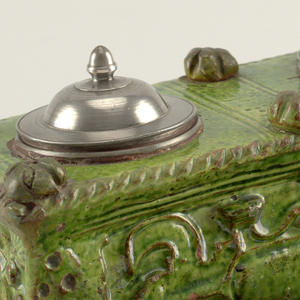Green inkwell, decorated in relief with rope and vine motifs, with two cups with metal lids on top and open shelf on bottom.