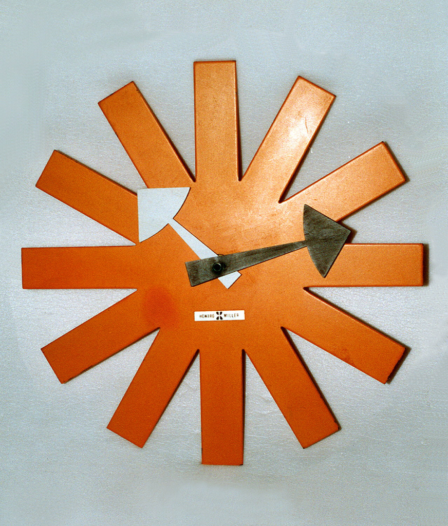 Clock in the shape of a large asterisk in bright orange, with a white hour hand and black minute hand in the shape of arrows. Mechanism housed in small circular body behind face.