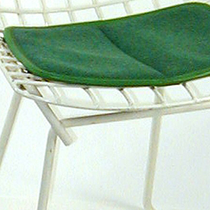 White child's chair, frame made of formed steel; four legs of the same steel are continuous, forming runners. Accompanied by a thin, green wool cushion.