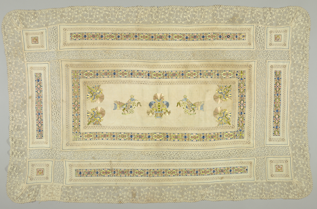 Central panel has embroidery in design of crowned birds on either side of a basket of flowers. Carnation ornaments in corners with borders of stylized flowers and drawn work.