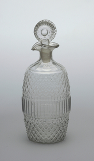 3-part mold blown, barrel-shaped body, central band of vertical flutes, diamond pattern above and below, flutes from shoulder to neck, everted lip with pouring spout, molded fluted bullseye stopper.