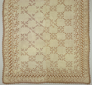 Oblong table cover of hand-woven linen of sheer open weave, embroidered in brown and white silk in cross stitch. Allover pattern arranged in squares of highly stylized floral or lily pattern; wide border of stylized vine. Edging of narrow brown and white silk lace. Linen is seamed at the center.