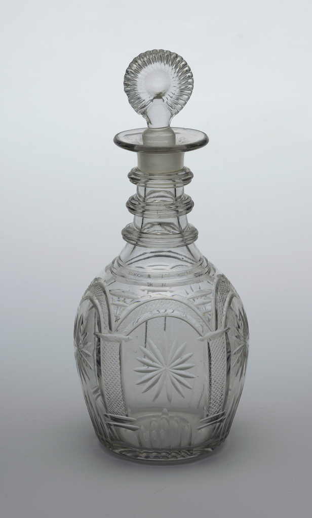 3-part mold blown (very hard to see), bulbous body with central panel in alternate section of vertical fluting and diamonds, fluting above and below 3 triple neck rings, wide lip, molded fluted bulls-eye stopper; pontil mark on bottom.