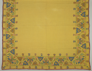 Square mustard-yellow linen cloth with a deep border repeat of symmetrical palmette and supporting leaves repeated alternately upright and reverse in heavy silks, cotton, metallic thread. Colors are pink, green, blue and gold.