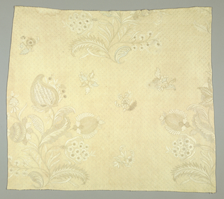 Fragment from a skirt or bedcover of fine cream-white quilting and embroidery with drawnwork details on linen. Ground is quilted with diagonal cross bars made from cord inserted in narrow ridges. Sections of large scale floral motifs, pomegranate and foliage.
