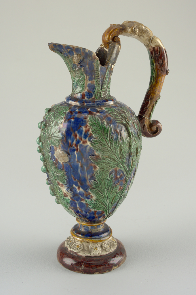Footed ewer in the style of Bernard Palissy.  Molded rosettes at foot. Bolded leaves and shells on body. Scrolling handle. Mottled blue and red ground with green leaves.
