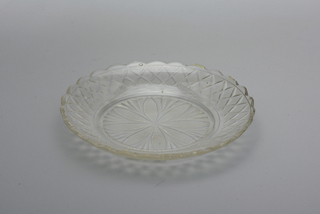 Circular plate with wide up-turned rim and scalloped edge; center cut with radiating petals filled with fine diamonds and fans between; rim cut with strawberry diamonds; glass bubbly.