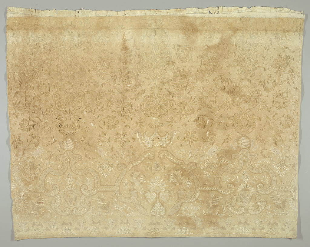 Panel of cream white trapunto with elaborate symmetrical design of flowers and drawnwork medallions in various stitches. Incomplete at top.
