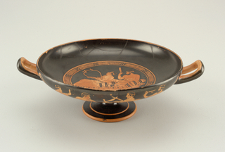 Shallow circular bowl on pedestal foot; two, squared-loop handles; black ground of Interior with central red-orange decoration showing scene of two youths reclining on couch, one lifting phiale, the other playing a lyre, the scene framed by a circular band of alternating key and checkerboard patterns.   Black ground of bowl exterior with red-orange decoration consisting of palmettes surrounding handles; between handles, on either side, tableaus of reveling youths on couches similar to scene in bowl.