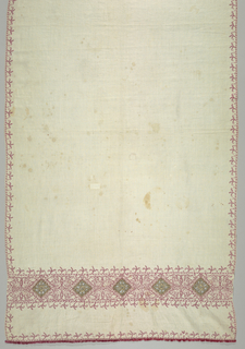Towel showing a floral band with needlework insets at each end and a floral border all around. Fringe at each end. Red silk on linen, insets in metallic thread.