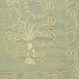 Long narrow sheer rectangular shawl with white-on-white embroidery. Floral vine border is continuous on all sides. At both ends, a large bunch of flowers tied together loosely with a ribbon fills the full width.