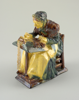 Figure of a woman dressed in dark green dress and cap with brown shawl and white apron, seated in a chair with lace-maker's pillow on her lap. A small piece of bobbin lace is attached to the pillow.