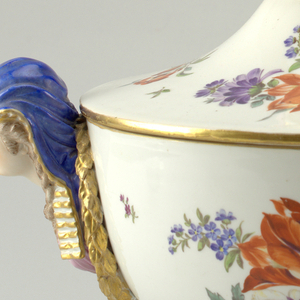 Tureen mounted on pedestal, being attached by brass bolt and nut. Pedestal with triangular foot and circular shaft; bowl of tureen decorated with two sphinx-head handles. Cover crowned with laurel leaves and seeds. Polychrome decoration of flowers and leaves.