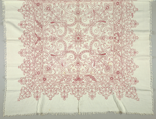 Design of a square radiating outward from a central flower and two borders embroidered in red and white. Red is used primarily for the chain stitch outline of the motifs while white is used for the filling stitches. Warp and weft fringe crossed and knotted on all four sides.