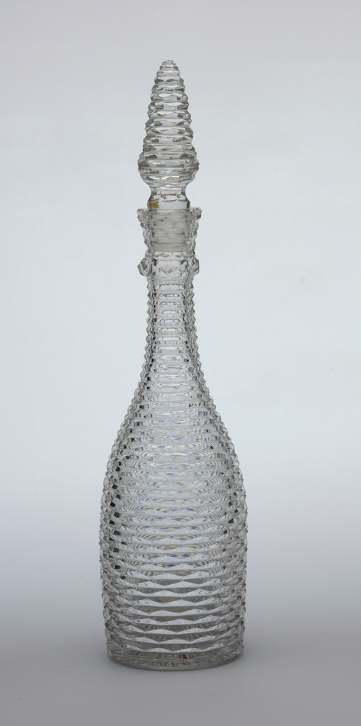 Bottle-shaped body with slender, ringed, neck. All-over decoration of chevrons in narrow horizontal bands. Stopper is conical with the same decoration.