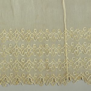 Skirt flounce with lower edge embroidered with a flat silk trimming in a pattern of arches, scallops and circles.