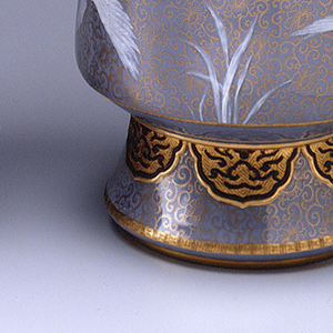 Cylindrical shape with long neck, flaring mouth and flaring cylindrical foot; two applied, gilt handles on neck, modelled as prunus branches; grey ground decorated with flying cranes in low relief in white slip, and with gilt oriental and arabesque designs with some touches of black.
