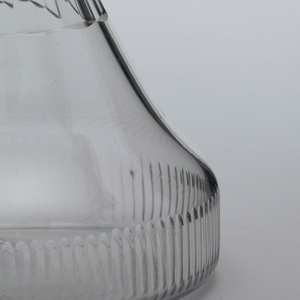 """""""Ship's decanter"""" type. Broad, flat base with cut comb flutes. Long tapered flutes interrupted by 3 flat neck rings. Flat projecting lip. Cut target stopper, with fluted neck."""
