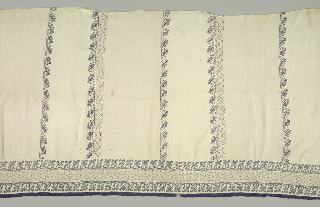 "White linen frontal made in eleven perpendicular panels of linen, which are outlined in narrow border of embroidery, stylized vine, in blue silks. Insertions of needlepoint lace, (four) also perpendicular; accross bottom a wider band of blue embroidery, a band of lace insertion, and another band of embroidery. Edged with narrow blue silk fringe. Stitch ""punto scrito"" - counted running."