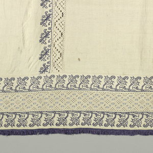 """White linen frontal made in eleven perpendicular panels of linen, which are outlined in narrow border of embroidery, stylized vine, in blue silks. Insertions of needlepoint lace, (four) also perpendicular; accross bottom a wider band of blue embroidery, a band of lace insertion, and another band of embroidery. Edged with narrow blue silk fringe. Stitch """"punto scrito"""" - counted running."""