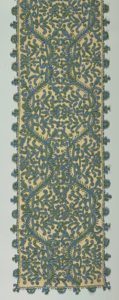 Long rectangular cover of tan plain weave linen embroidered with a horizontally and vertically symmetrical pattern related to an ogee grid enclosing flowers using blue and green linen. Edges decorated with needle-made lace tabs worked directly over the edges of the foundation, using the same blue and green linen as the embroidery.