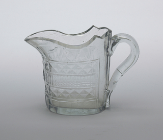 Straigh-sided oval body with shaped lip, pouring spout, notched loop handlesides cut with sallow faceting under lip, then bands of diamonds, vertical flute, diamonds and wide flutes; a star on the bottom; glass bubbly, bluish