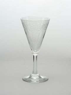 Cone-shaped wine glass engraved with swirl pattern.