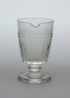 """Goblet-shaped, with straight, slightly flaring sides, on a spool stem with central knop, thick flat circular foot, a pouring spout at lip; cut with vertical flutes bottom of sides, above that a band engraved with """"CORK CORPORATION"""" and fine diamonds; ground pontil mark bottom."""