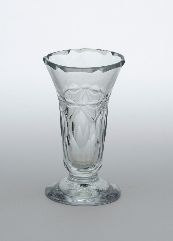 Deep flute-shaped bowl with flared lip, on domed, spreading foot; cut with 2 rows of printies, row of smaller printies above lip cut with shaped facets, edge of foot with row of facets; ground pontil mark bottom; glass of bluish cast.
