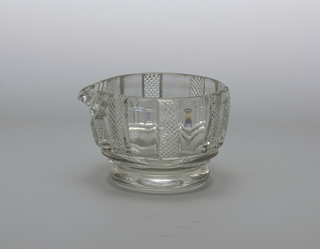Round bowl with a pouring lip, cut with vertical pillar flutes alternating with small diamonds, 2 prismatic bands below, a short round foot, ground pontil mark bottom.