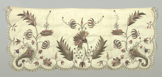 Short wide apron of white embroidered in silver thread, rose, violet and white. Design is a large central flower spray of carnation and lily with leaves in silver thread. Corner design of cornucopia with sprays of tulips and lilies. Bottom and sides have a subtle scallops bordered in a sawtooth pattern in silver thread.