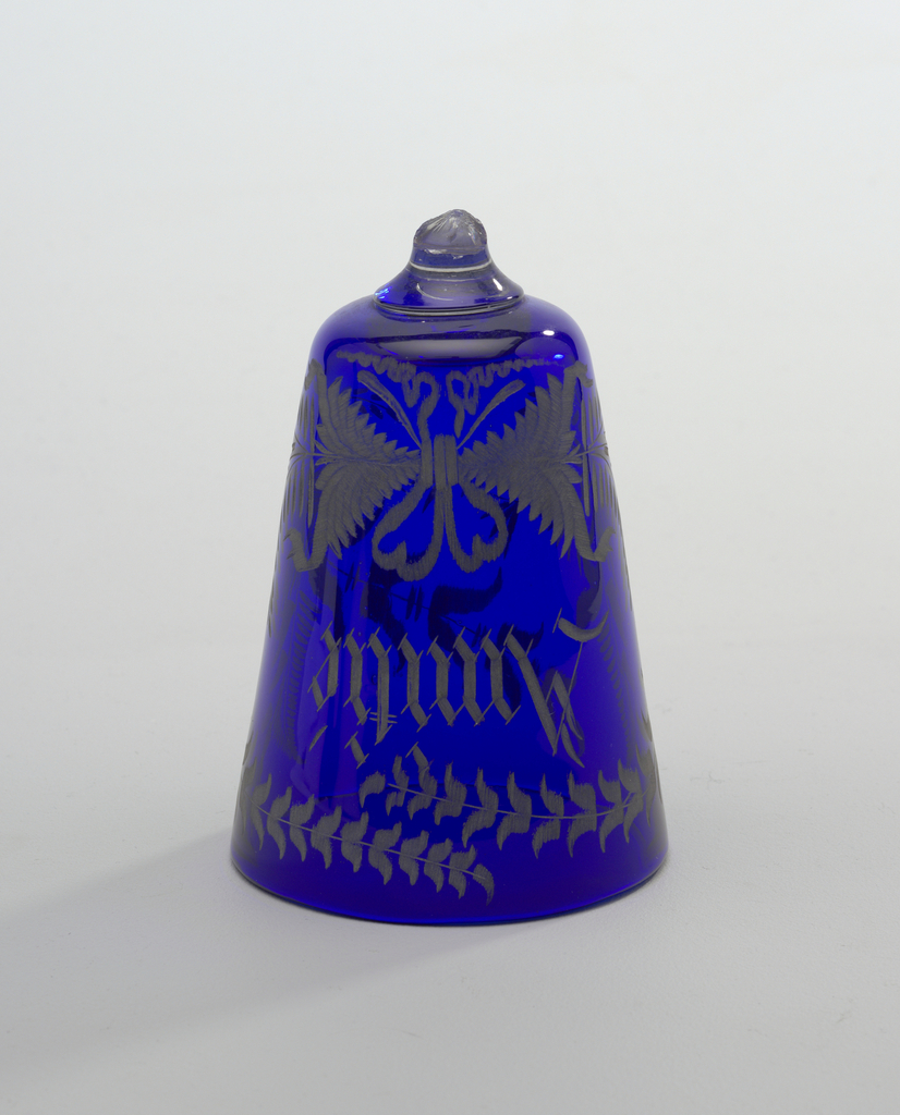 """Bowl in blue glass, with straight-flaring sides, rounded at bottom; fragment of attached stem in clear glass. Bowl is coarsely engraved in spray of leaves tied with a ribbon at center and forming a wreath enclosingthe word """"AMITIE"""" in sharply spurred Old English letters. Engraved areas colored in dull surfaced yellowish silver."""