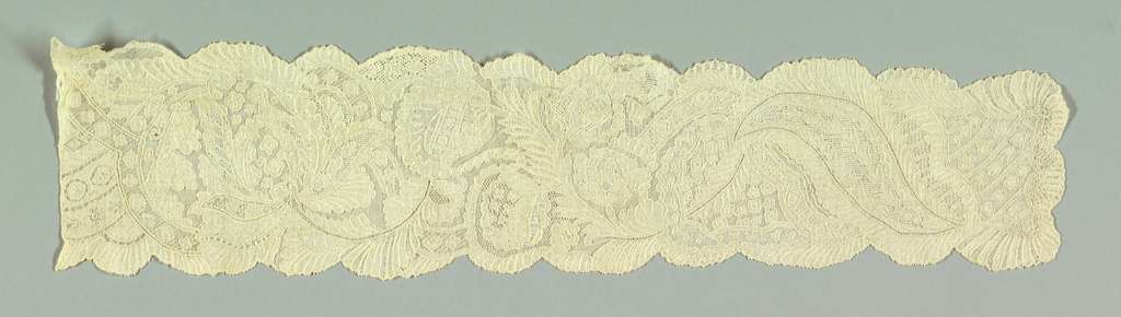 Design shows serpentine garland of floral and foliated forms, accentuated by intermittent parallel bands; interpretation of a French pattern. Drawnwork combined with embroidery; outlined by cordonnet.