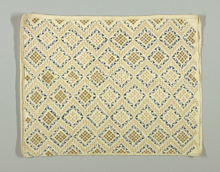 Woven linen pillow cover showing an allover diamond pattern with dark yellow and blue embroidery.