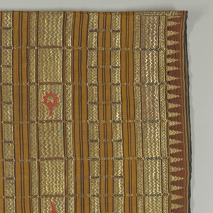 """Length of material in tube form, seamed up one side. Reddish brown, black, and amber woven warp (vertical) stripes with heavily embroidered horizontal stripes in gold thread. Some horizontal bands feature vertical stripes within them, which alternate with the few vertical stripes that run the length of the piece. Bottom edge has row of triangles embroidered in gold thread. Row of appliqué artichokes (?) in pink about 30.5cm (12"""") from the bottom."""