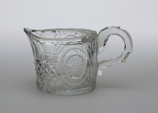 Oval straight-sided body with extended pouring and in-turned top lip; wide loop handle notched; sides cut with 2 encircled stars either side of handle, around the front wit a band of diamonds. flutes above; heavy' glass clear.