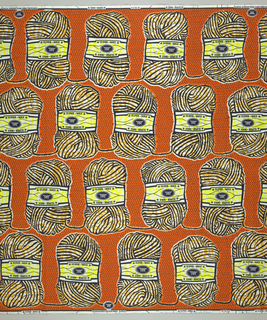 Skeins of yarn with paper labels reading Super Wax with Vlisco label. Printed in indigo, ochre, yellow and orange.