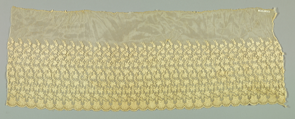 Net embroidered in running stitch in pattern of curving stem with flowers and leaves.